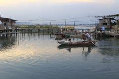 渔夫乘小船努力去做在微明 库存照片