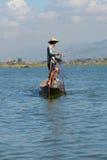 渔夫乘木小船解开一个捕鱼网 湖Inle,缅甸 免版税图库摄影