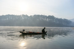 渔夫人行在湖的小船渔夫人的工具,他们使用这一个为他们的工作,在有雾 图库摄影