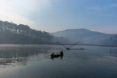 渔夫人行在湖的小船渔夫人的工具,他们使用这一个为他们的工作,在有雾 免版税库存图片