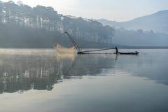 渔夫人行在湖的小船渔夫人的工具,他们使用这一个为他们的工作,在有雾 库存图片