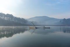 渔夫人行在湖的小船渔夫人的工具,他们使用这一个为他们的工作,在有雾 免版税库存照片