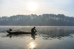 渔夫人行在湖的小船渔夫人的工具,他们使用这一个为他们的工作,在有雾 免版税图库摄影