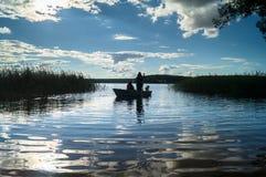 渔夫剪影划艇的,漂浮往湖岸在盲目的阳光下 塞利格,俄罗斯 库存图片