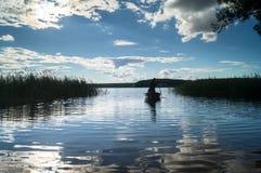 渔夫剪影划艇的,漂浮往湖岸在盲目的阳光下 塞利格,俄罗斯 库存照片
