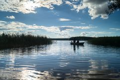 渔夫剪影划艇的,漂浮往湖岸在盲目的阳光下 塞利格,俄罗斯 免版税库存照片