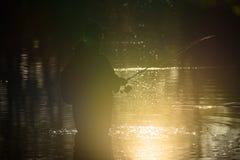 渔夫剪影在湖,在日落期间 免版税库存图片