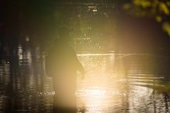 渔夫剪影在湖,在日落期间 免版税图库摄影