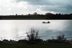 渔夫剪影小船的在拉特兰湖,英国 免版税库存照片