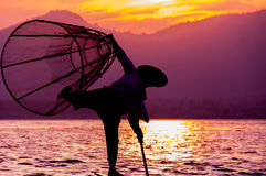 渔夫剪影日落Inle湖的 免版税库存图片
