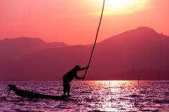 渔夫剪影日落Inle湖的 库存照片