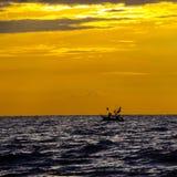 渔夫剪影有小船钓鱼的 库存图片