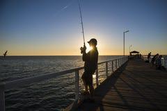 渔夫剪影有站立在海船坞渔的帽子和鱼标尺的在与美丽的橙色天空的日落在假期放松 免版税库存图片