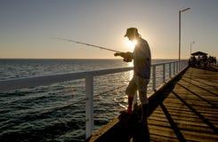 渔夫剪影有站立在海船坞渔的帽子和鱼标尺的在与美丽的橙色天空的日落在假期放松 库存照片