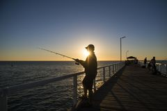 渔夫剪影有站立在海船坞渔的帽子和鱼标尺的在与美丽的橙色天空的日落在假期放松 库存图片