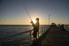 渔夫剪影有站立在海船坞渔的帽子和鱼标尺的在与美丽的橙色天空的日落在假期放松 免版税库存照片