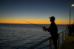 渔夫剪影有站立在海船坞渔的帽子和鱼标尺的在与美丽的橙色天空的日落在假期放松 图库摄影