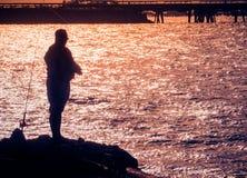 渔夫剪影有被反射的闪耀的海水的 免版税库存照片