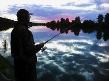 渔夫剪影有钓鱼竿的在日出的湖 美丽如画的五颜六色的第一太阳光芒 免版税库存图片