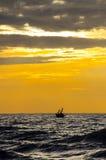 渔夫剪影有钓鱼他们的小船的,当sunris 库存照片