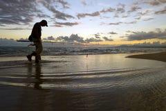渔夫剪影海滩日落 免版税图库摄影