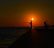 渔夫剪影由海的日落的 库存照片
