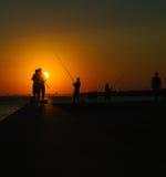 渔夫剪影由海的日落的 免版税库存照片