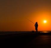 渔夫剪影由海的日落的 库存图片