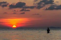 渔夫和一艘船剪影在背景在日落 免版税库存照片