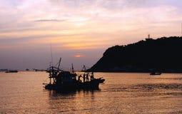 渔夫和小船剪影在海湾的 库存图片