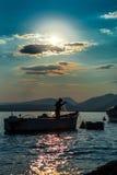渔夫和小船剪影 库存照片