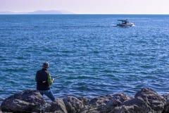 渔夫和小船在海 堤防在伊斯坦布尔 免版税图库摄影