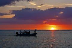 渔夫和狗在一条小船在日落-佛罗里达 免版税图库摄影
