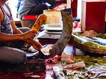 渔夫在一常设刀片boti的切口鱼在一个木树桩帮助下在印地安鱼市上在kolkata 库存照片