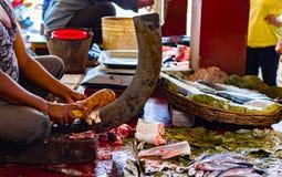 渔夫在一常设刀片boti的切口鱼在一个木树桩帮助下在印地安鱼市上在kolkata 库存图片