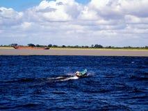 渔夫在两之间的横穿合流区分了河 免版税库存照片