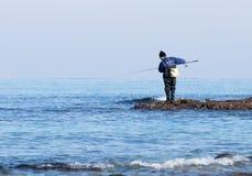 渔夫在冬天早晨抓在一转动的一条鱼 免版税库存照片