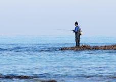渔夫在冬天早晨抓在一转动的一条鱼 免版税库存图片