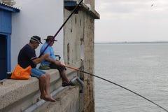 渔夫在卡迪士海口的港口钓鱼  免版税库存图片