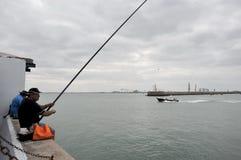 渔夫在卡迪士海口的港口钓鱼  免版税图库摄影