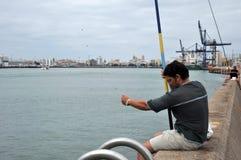 渔夫在卡迪士海口的港口钓鱼  库存图片