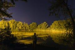 渔夫在夜,夜渔,鲤鱼标尺,在湖的繁星之夜反射 库存照片