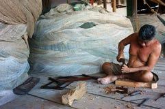 渔夫在捕鱼网商店削去木头。CA MAU,越南6月29日 免版税库存照片