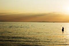 渔夫在日落的海 免版税库存照片