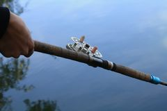 渔夫在晚上抓在葡萄酒钓鱼的一条鱼 免版税库存照片