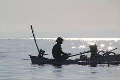 渔夫在朝阳耐心地等待 免版税库存图片