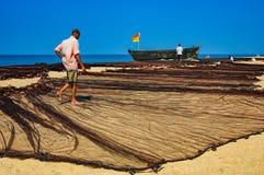 渔夫在果阿,印度烘干了他的老渔夫` s网 免版税库存图片