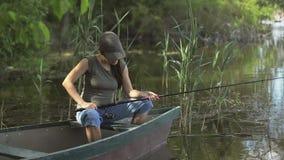 渔夫在森林湖钓鱼的年轻女人,拿着钓鱼竿扭转卷 股票视频