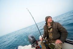 渔夫在海捉住一条三文鱼 库存照片