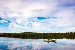 渔夫在湖的一条绿色小船航行 免版税库存图片